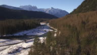 Nature Drone Shot of River in Mountain Forest with Fresh Powder Snow and Blue Sky video
