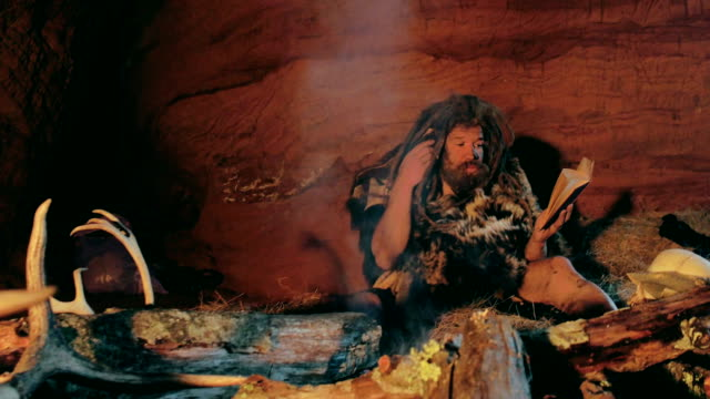 Neanderthal man reads old book near bonfire in his cave video