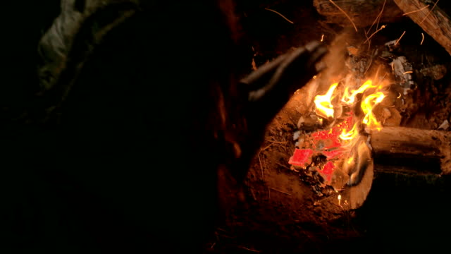 Neanderthal man warms his hands by the first bonfire in his cave video