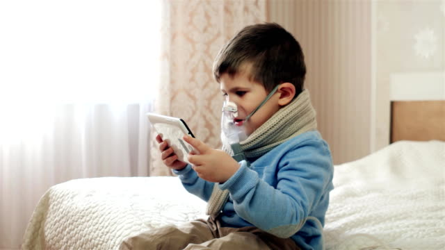 Nebulizer for inhalation, kid with an oxygen mask on his face, sick child breathes through nebulizer, boy does inhalation, treatment at home video