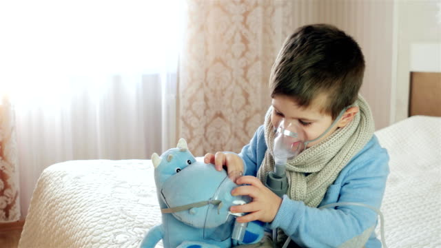 Nebulizer for inhalation, sick child breathes through nebulizer, baby does inhalation, boy with an oxygen mask on his face, treatment at home video