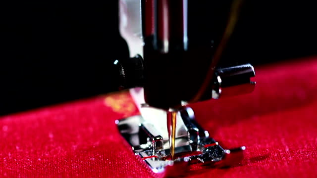 Needle with thread stitching seam on fabric. Working sewing machine video