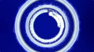 Neon Blue Light with Sparkle and Smoke Trail Creates Multiple Round Metallic Three-dimensional Rings. Dark Blue Background. video
