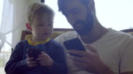 Nephew and uncle plays games together on phones video