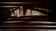 Nervous young woman peers anxiously through blinds, looking left, right and at the camera. video