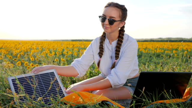 new technology, girl recharges laptop using solar battery on field of sunflowers, young woman applying solar photovoltaic panels video