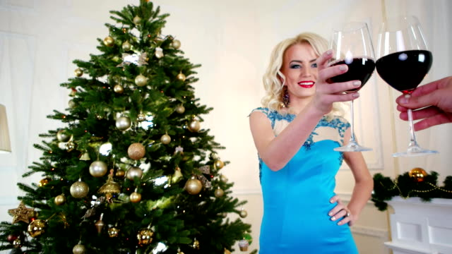 New Year's Eve toast holiday, beautiful girl is drinking wine, smiling, having fun on a Christmas party in a festive dress near the Christmas tree on New Year's Eve celebration video