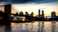 New York timelapse with Brooklyn Bridge going through sunset, twilight and night, while boats sail the East River. video
