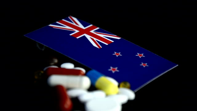 New Zealand flag with lot of medical pills isolated on black background video