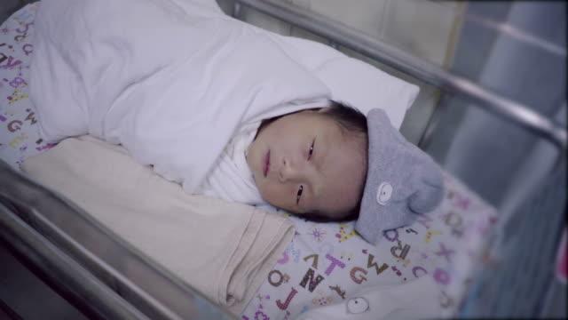 Newborn Asian Baby Sleep In Incubator With Baby Blanket. video