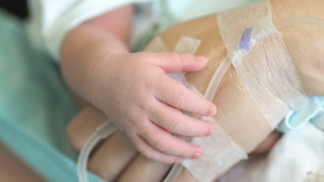 Newborn baby holding mother hand with saline solution video