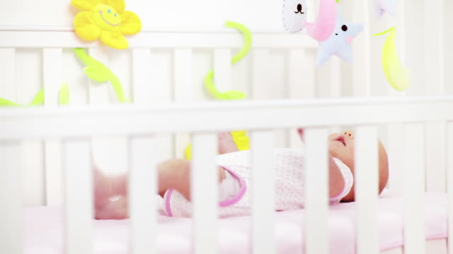 Newborn girl playing with toys in crib video