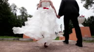 Newly married couple walk on park holding hands video