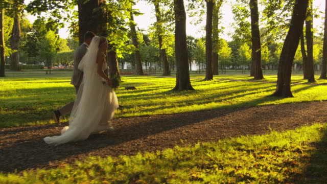 Newlyweds are running in the park. video