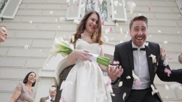 SLO MO Newlyweds being showered with roses when leaving church video