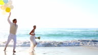 Newlyweds laughing and playing with balloons on the beach video