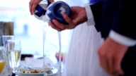 Newlyweds pour colorful sand in glass during wedding celebration video