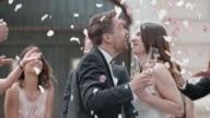 SLO MO Newlyweds toasting and kissing in rose petal shower video