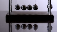 Newtons cradle in motion on reflective surface video