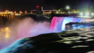 Niagara Falls at night. The jets of falling water are illuminated with colored spotlights. The flow of water on a dark foreground video