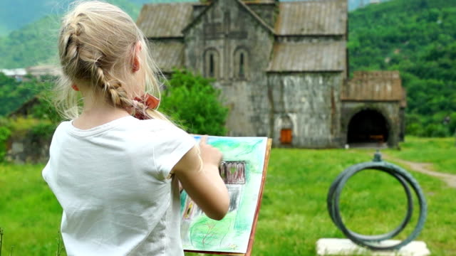 Nice blonde schoolgirl drawing picture by chalk in the open air video