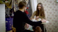 Nice couple of young people in the cafe talk. Girl smiling at her boyfriend, she drinks coffee, warm hands. Beautiful brunette little bit confused and in love video