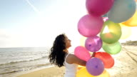 nice girl playing with balloons on the beach video