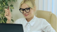 Nice girl smiling and looking at computer screen in office video