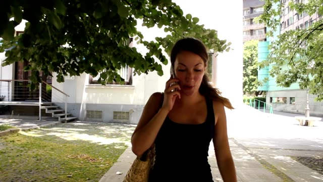 Nice girl talking over the phone happy in town video