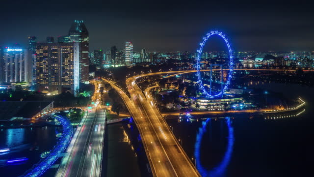 night light traffic road and famous singapore flyer 4k time lapse video