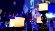 Night party. Golden candelstick. 4 lighting candels, people dancing video