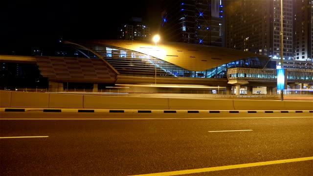 Night shot, time lapse of Dubai Street car traffic and metro station video