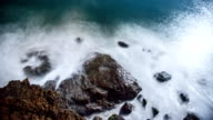Night Timelapse of Waves Splashing against Rocks, illuminated by the Moon. Long Exposure and Motion Blur. video