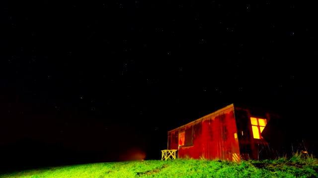 Night time-lapse with a shack and a starry sky video