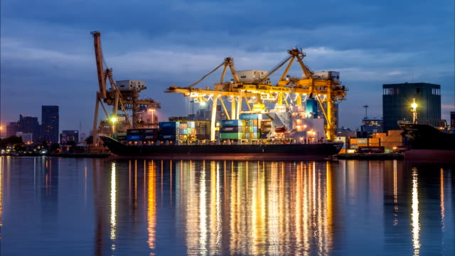 Night to day of  Container Cargo freight ship with working crane bridge in shipyard video