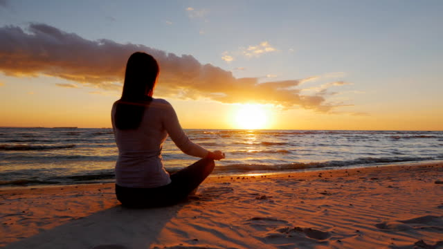 No stress. Calm young woman sitting in a lotus position on the beach at sunset video