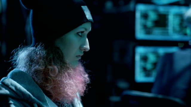 Nonconformist Teenage Hacker Girl with Pink Hair Attacks Corporate Servers with Virus. Room is Dark, Neon  and Has Many Displays. video