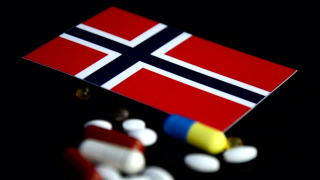 Norwegian flag with lot of medical pills isolated on black background video