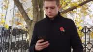 November 18 2016, Birmingham/UK: Man Wearing Remembrance Day Poppy Using Mobile Phone video