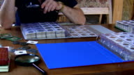 Numismatist examining coin collection video