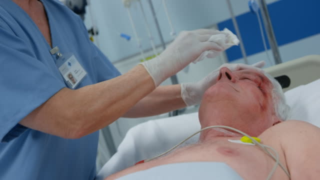 Nurse bathing a senior man lying in the intensive care unit video