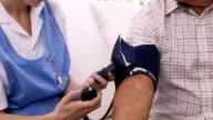 Nurse checking bloody pressure of senior man video