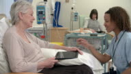 Nurse Checking On Senior Female Patient Having Chemotherapy video