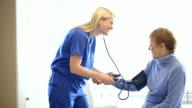 Nurse checking senior woman's blood pressure video