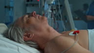 Nurse checking the monitor parameters of male patient in ICU video
