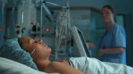 DS Nurse checking up on female ICU patient video