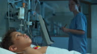 DS Nurse checking up on small boy in intensive care video