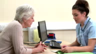 Nurse Discussing Test Results With Senior Female Patient video