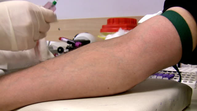 Nurse drawing blood samples from man vein for a test video