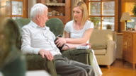Nurse explaining blood pressure measuring to senior man at home video